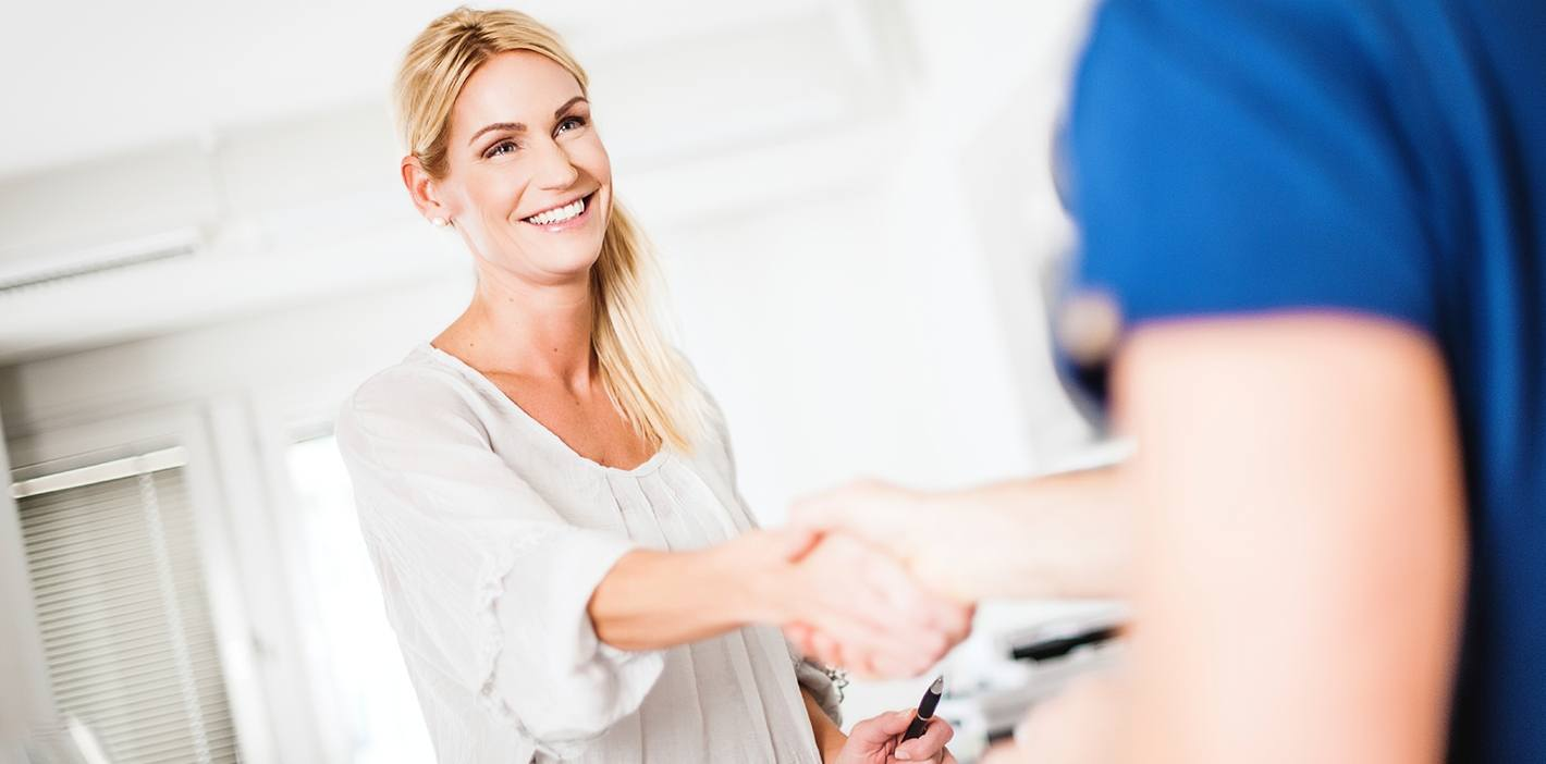 Smiling woman shaking hands with dentist
