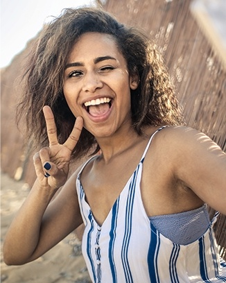Smiling woman giving peace sign