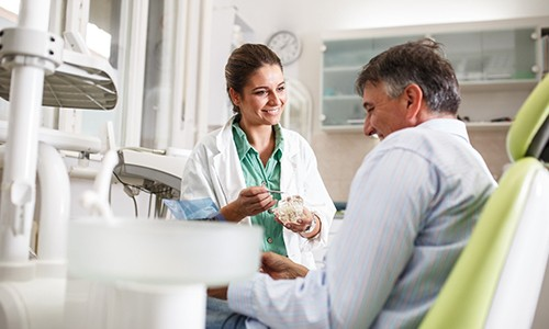 Dentist smiling and talking to patient before treatment