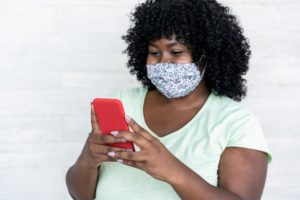 person calling their dentist in Big Pine Key to schedule an appointment while wearing a mask