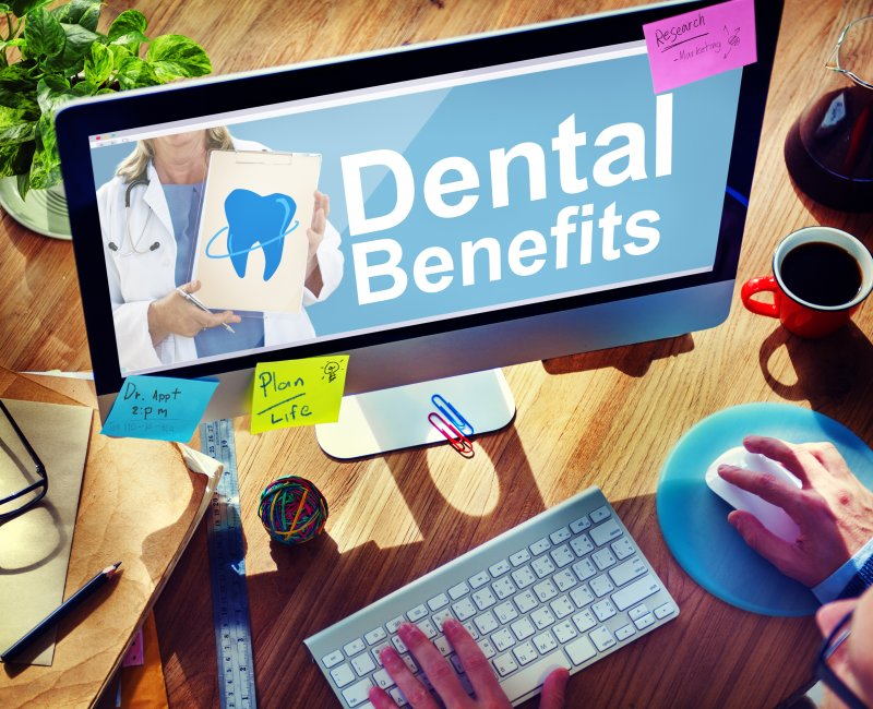 Patient researching dental insurance benefits on laptop