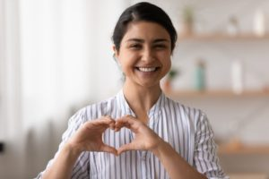Making heart shape, thinking about connection between gum disease and heart disease